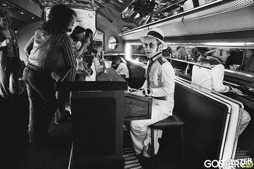 Elton John at the piano bar aboard his private plane - 1976